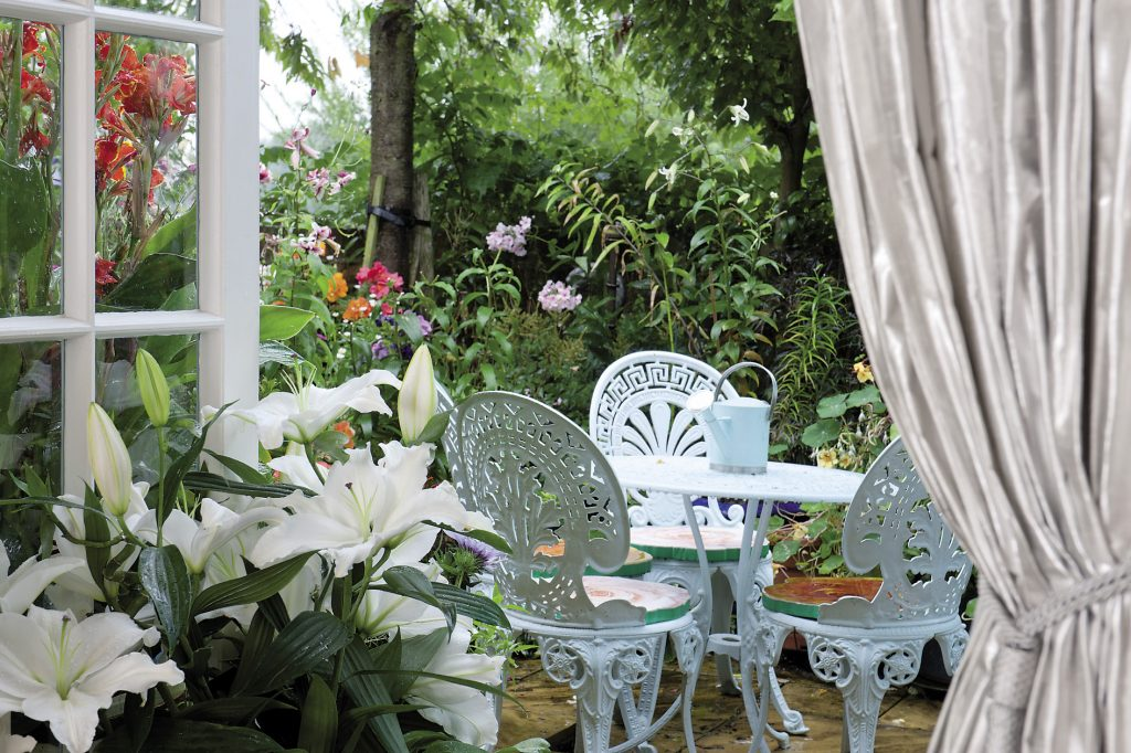 ...French doors leading out to Erica's patio garden where climbing roses, lilies, jasmine, sweet peas, clematis and a dozen of their friends and relatives jostle for pride of place...