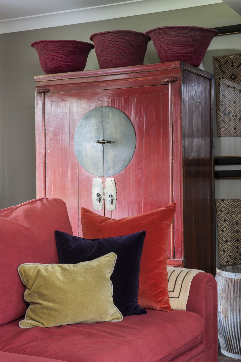 To the left of the woodburner, echoing the vibrant red of the sofa in front, stands a striking Chinese wedding cabinet