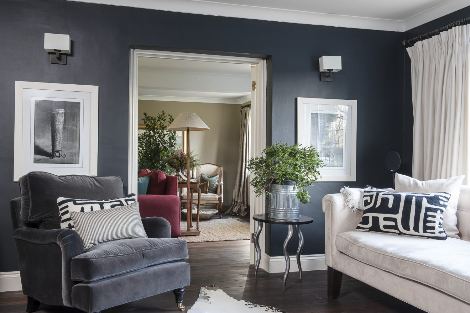 """The walls of the grown-ups' snug, painted in Farrow & Ball 'Off Black', creates an inviting and cosy evening retreat. """"I often think darker colours are more neutral than white,"""" says Adele. """"They often make spaces look larger rather than smaller and add depth and warmth."""" The sofa is flanked by two superb tables with brushed aluminium legs in the shape of kudu horns"""