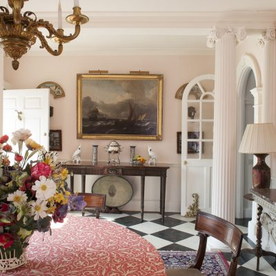 The large reception hall and dining room features a handsome marble fire surround, a marble bust on a tall plinth and a pair of marble-topped tables and walls painted in Pink Ground by Farrow & Ball
