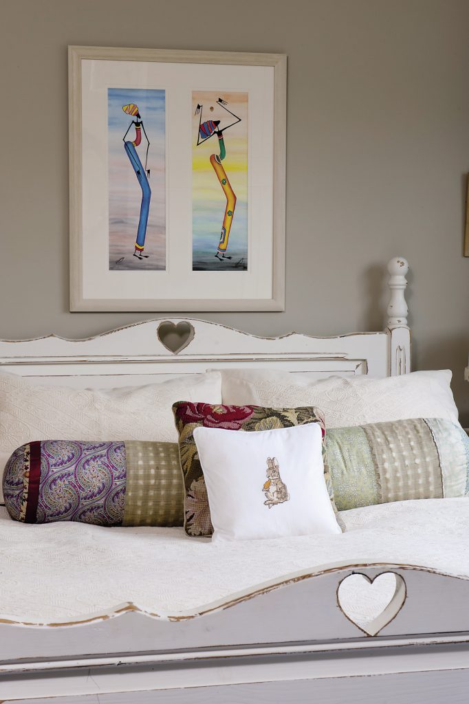 The guest bedroom is painted in Farrow & Ball's Stony Ground and simply furnished with a carved wooden bed and a pair of painted bedside tables