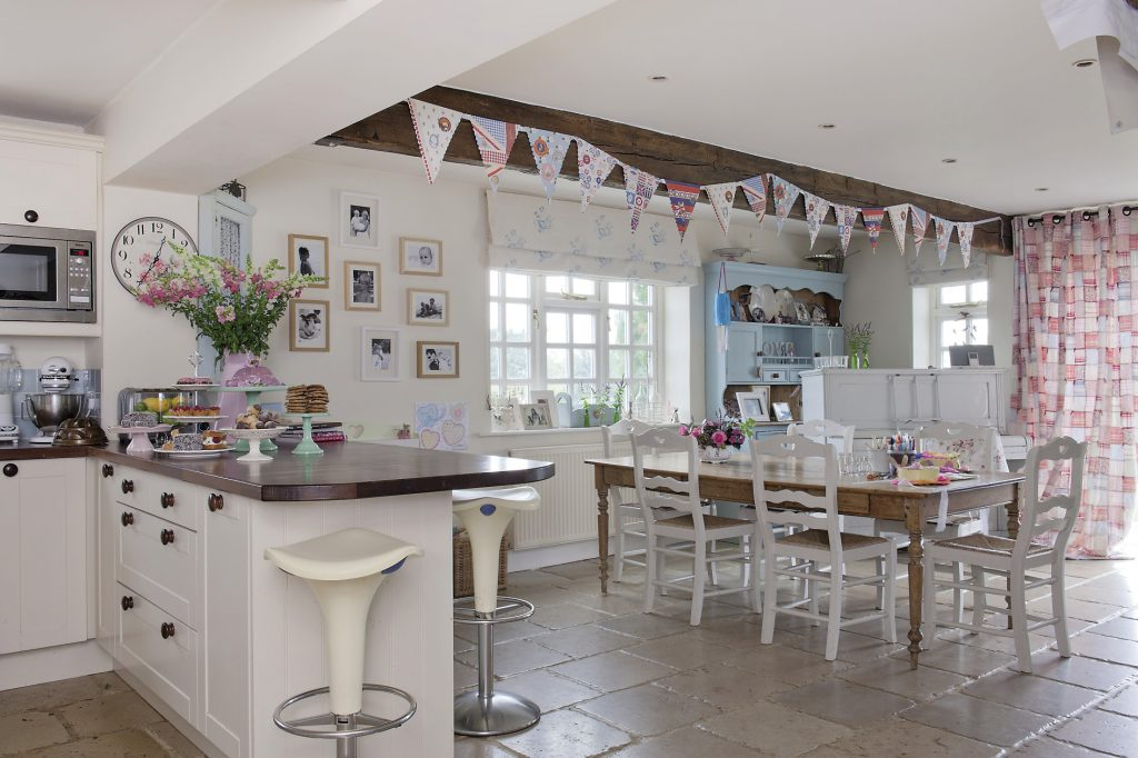 The open plan kitchen/breakfast room is painted a chalky white and the low beams are decorated with colourful bunting and pretty striped ribbons from which the children's vivid paintings and drawings are hung