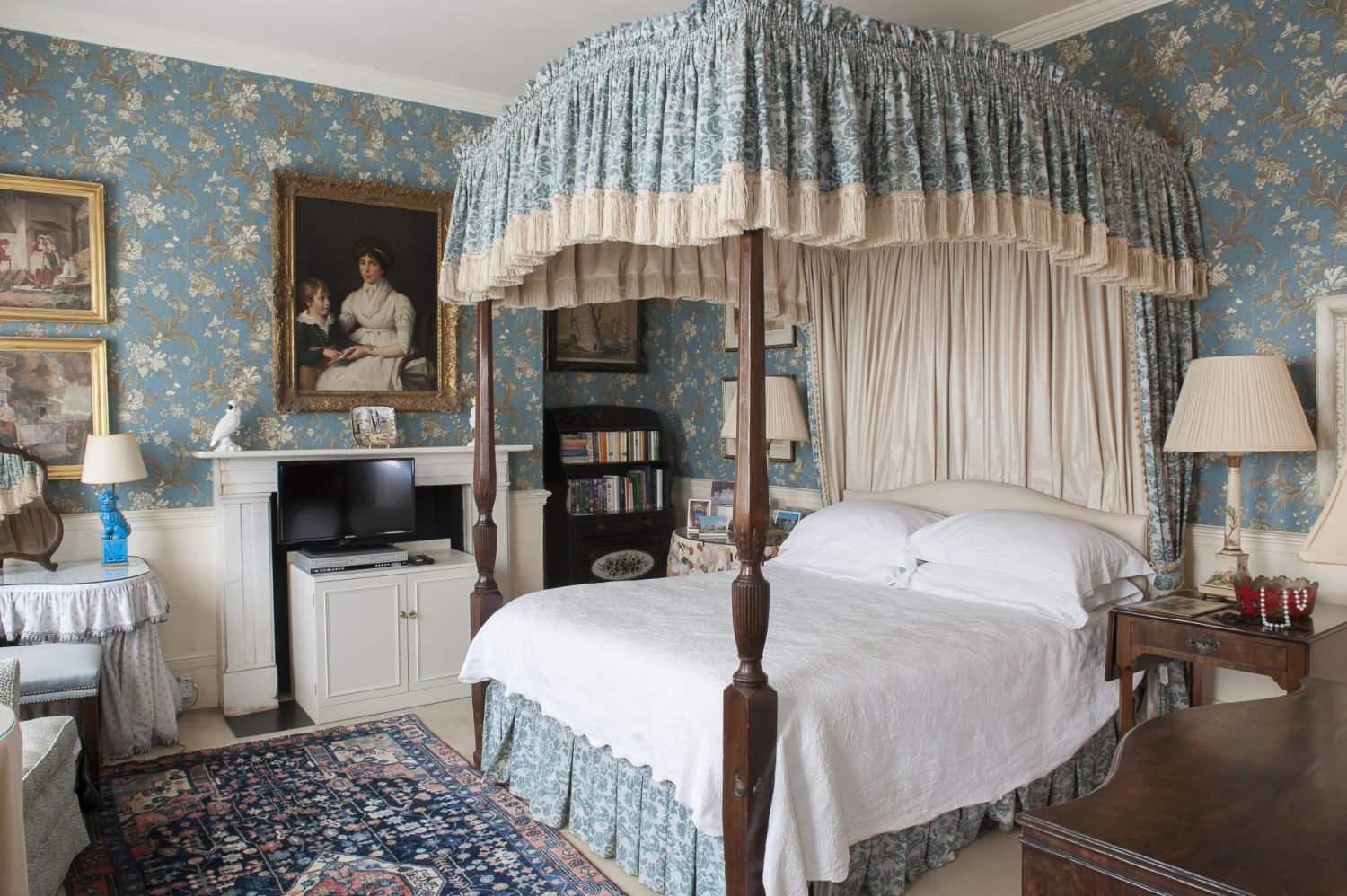The impressive Blue Room, with its slate blue French wallpaper, looks reminiscent of a Colonial American style