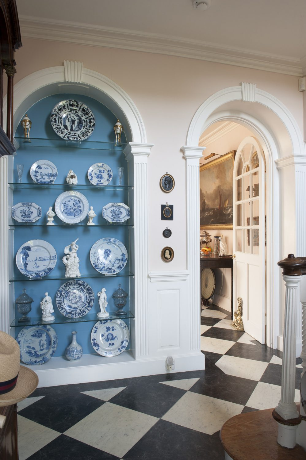 A collection of 18th century English Delft plates is framed by a blue alcove