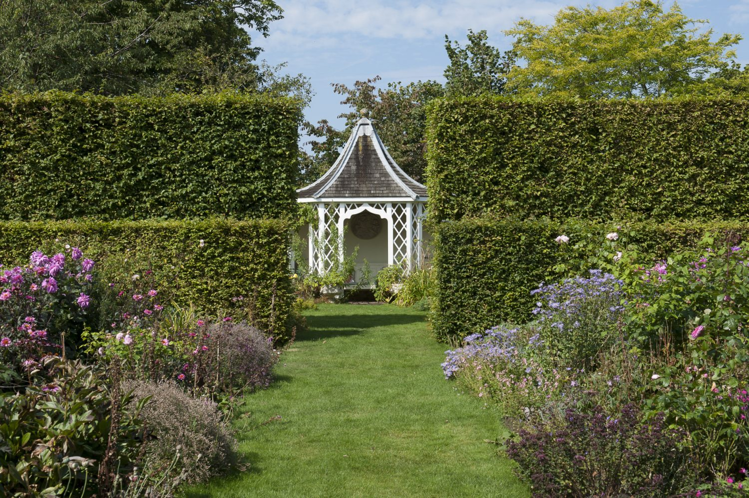 The bell-shaped summerhouse with its delicate trellis sides peeps through the gap in the hornbeam hedge