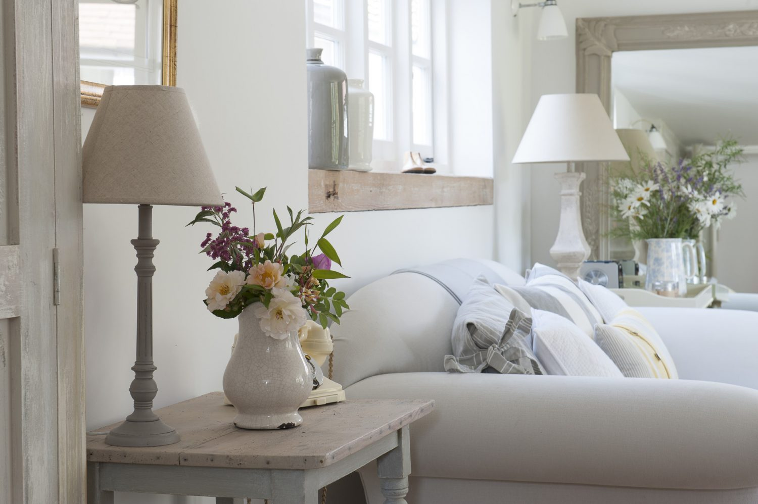 The bright and airy sitting room is completed with shades of greys, creams and yellows provided by the soft furnishings. Farrow & Ball's 'All White', used throughout the house, cleverly provides subtle variations of shade depending on the quality of the light and the angle it strikes wall or ceiling