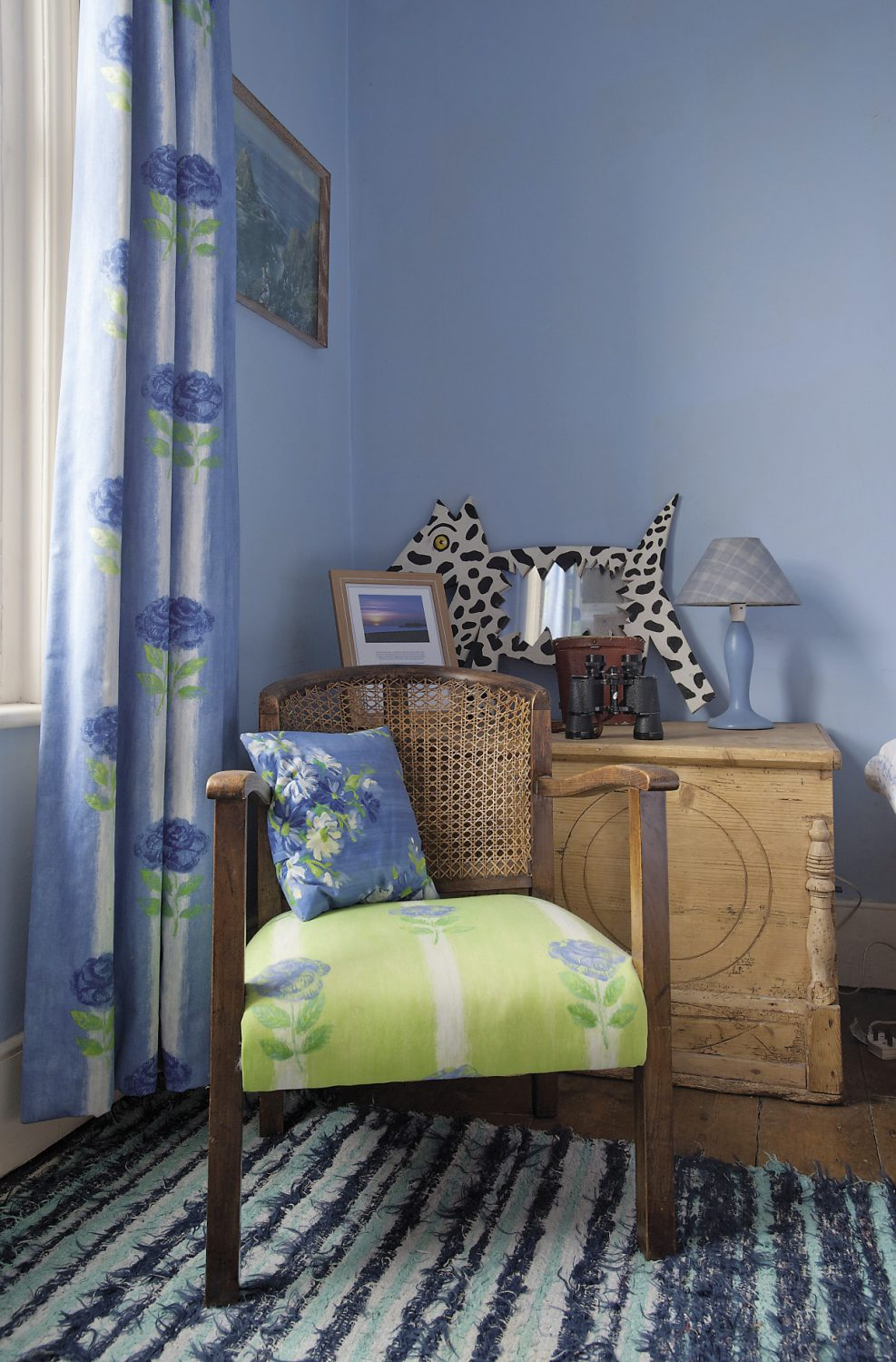 The guest bedroom is painted a strong forget-me-not blue. A low, cane-backed chair is upholstered with a cobalt blue and lime green Designers Guild fabric, the reverse colourway of the curtains, and there are more bright green accents around the room