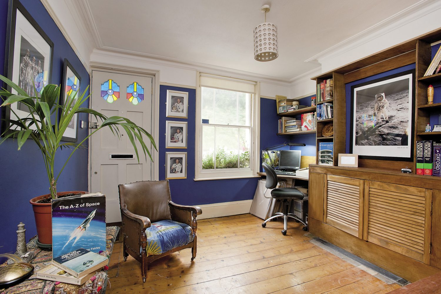 In the study, Alastair has constructed his own bespoke desks and bookshelves and the dark blue walls are covered in photographs from America's space missions of the 1960s and 70s