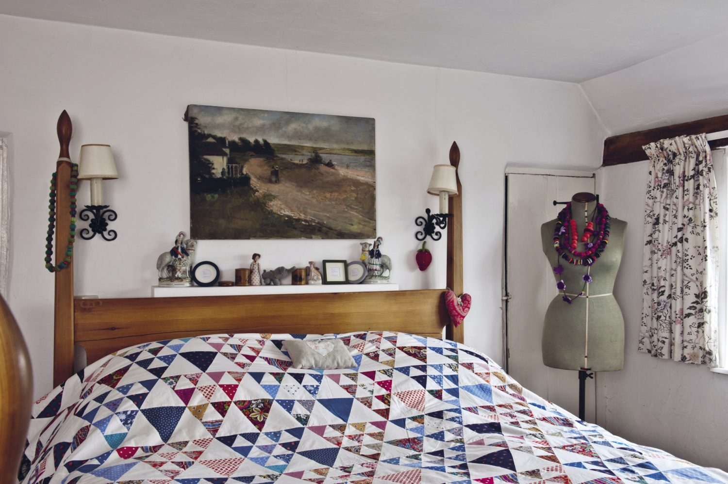 The main bedroom features a wooden Shaker-style bed that was handmade by a local craftsman and covered with a patchwork quilt with a border of heart, animal and house motifs that Nancy made
