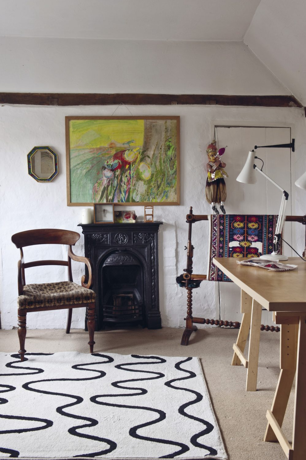 In the second bedroom one of Roger Nicholson's later paintings hangs above the fireplace. The composition is more abstract and the colours are arresting. Vivid scarlet, lime and gold are juxtaposed with rose pink and lilac. The colours seem to shimmer as if with the heat of a summer's day