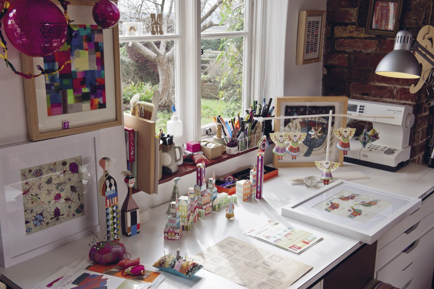 Nancy's 'Little City' paper kit buildings are grouped together on her desk as if on a tiny street