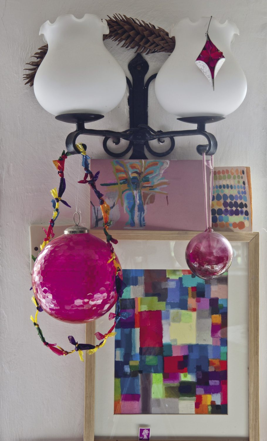 Designs and paintings created by Nancy nestle between three windows which take up most of the wall above her desk. Each one is saturated with carefully chosen colours