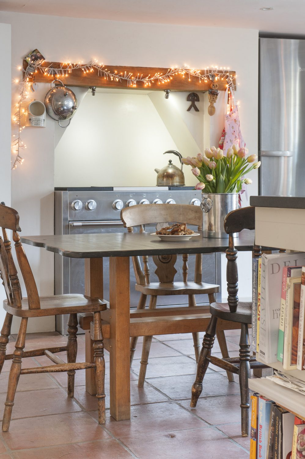 The cottage kitchen is tailor-made Shaker with black granite surfaces that complement the slate kitchen table that was once a potting table from a greenhouse in Brighton. The cooker is a serious Mercury range, a testament to Adrian's skills as a chef