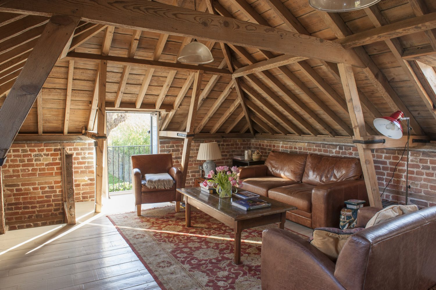 The couple have divided the upstairs space with a spacious kitchen at one end and, at the other, a relax-and-chill area with deep leather sofas from the Sofa Workshop and Trading Boundaries in Fletching