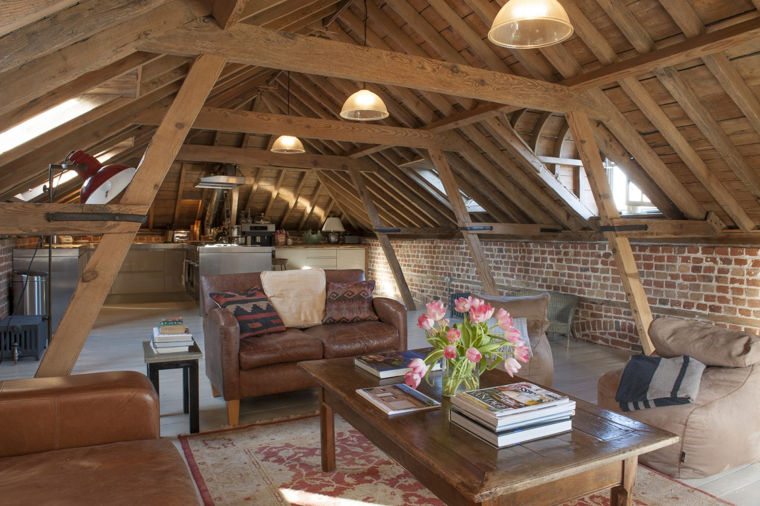 The spectacular space that was once the hay loft boasts superb 230-year-old timbers, every inch now sandblasted and lovingly waxed by hand to a honeyed glow. The only part of the building the couple were unable to save were the floorboards that have now been replaced with irregular-sized painted boards