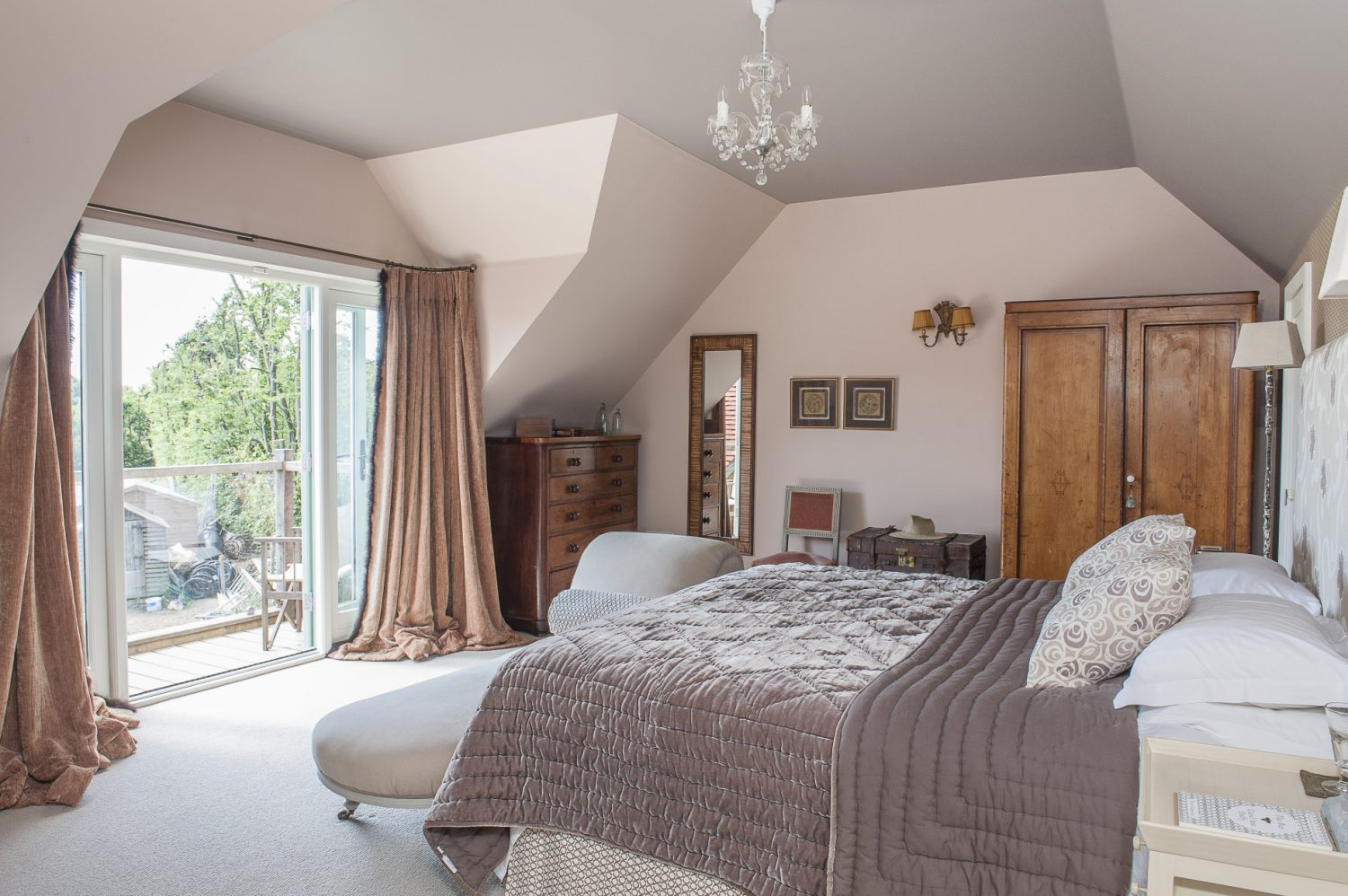 In the master bedroom, with its own balcony, the elegant bed is surrounded by a glowing mahogany chest of drawers and an elegant cherry gentleman's wardrobe