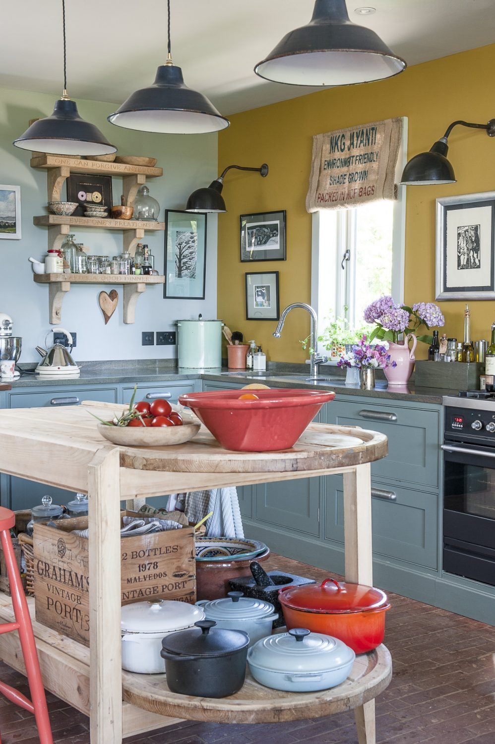 Visitors pass through the hallway into a spacious kitchen/dining room where Philippa's enviable flair for pulling-off imaginative colour combinations is evident in the contrasting shades of faded teal and mustard yellow that she has chosen to paint the units and walls