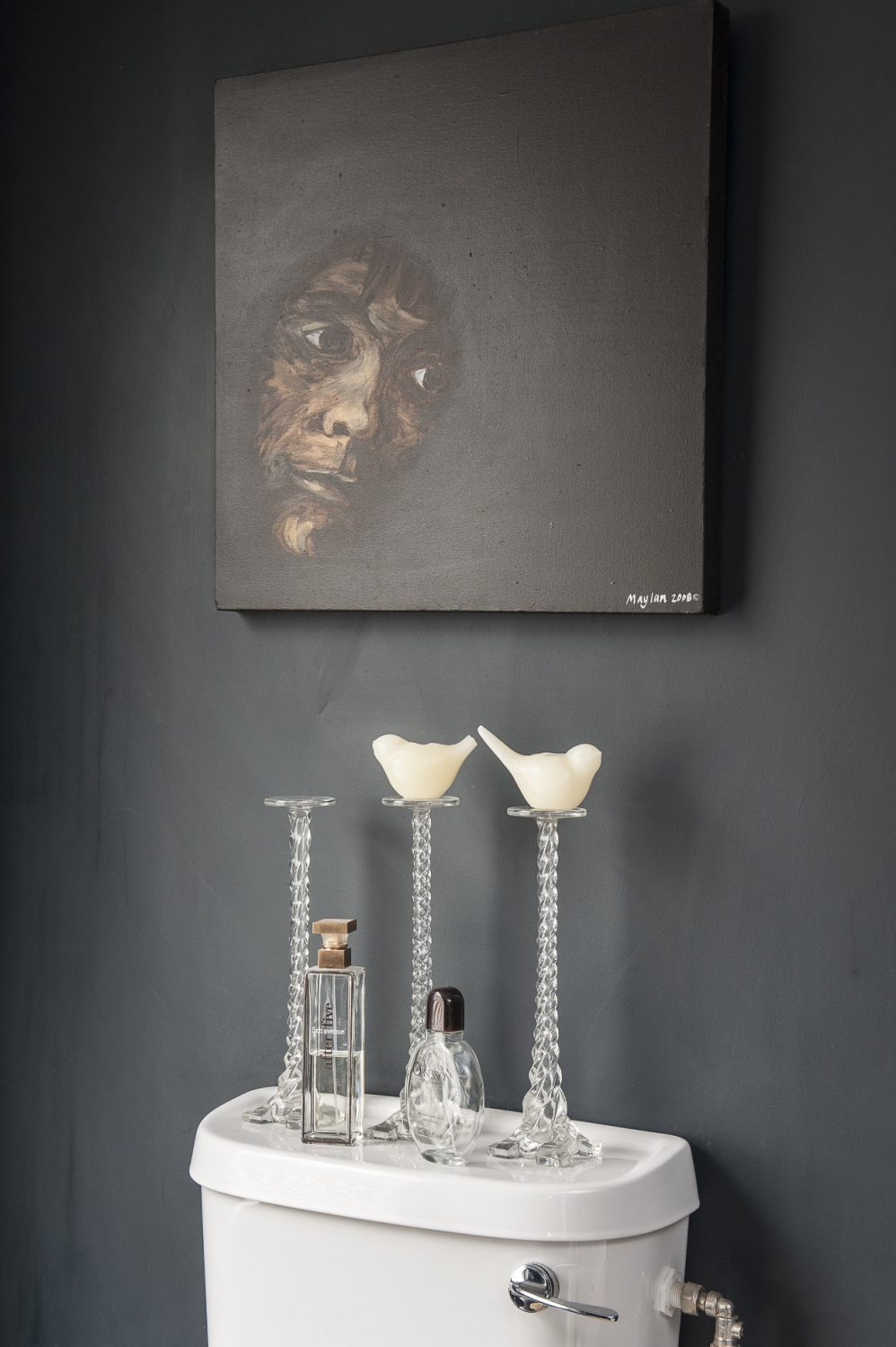 There are two good-sized rooms – one white and one black – both have a striking painting in a similar position; in the white bathroom there's a picture of a skull by Ben Eine and in the black, a raw and intense painting by Alice Maylam titled 'Out of the Dark' which features a face protruding into the light and provided the inspiration for Rob's bold colour choice
