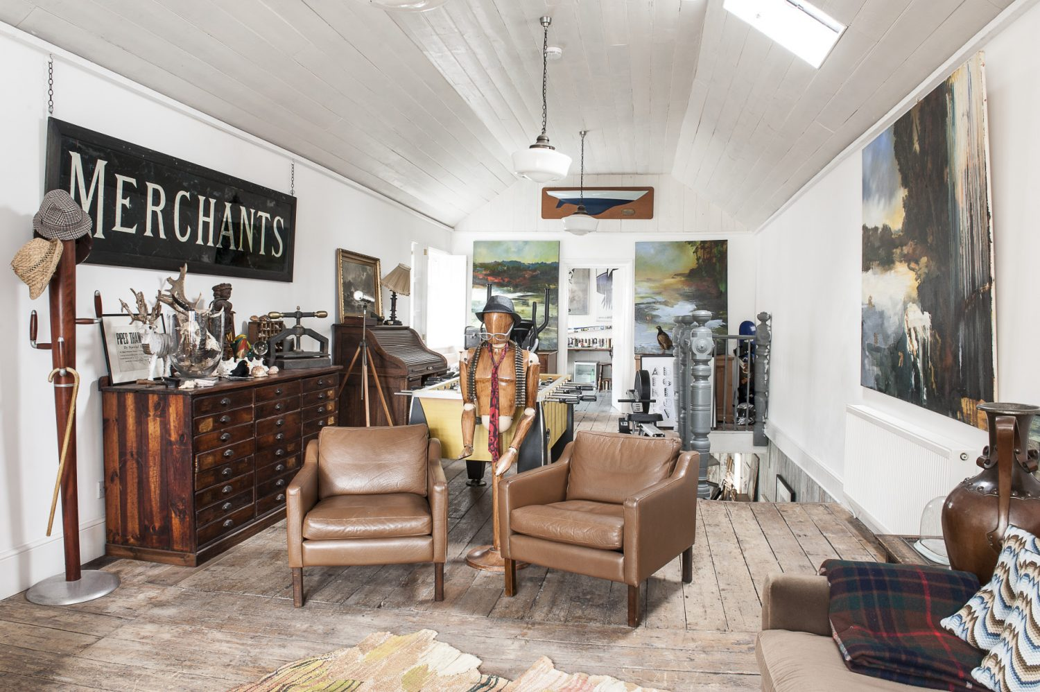 The open-plan living area is home to part of Rob's collection of artworks. The paintings are almost overwhelming in their power and the house with its tall, predominantly white walls and delicate, scraped back detailing, recedes modestly and elegantly into the background to allow the paintings their full presence