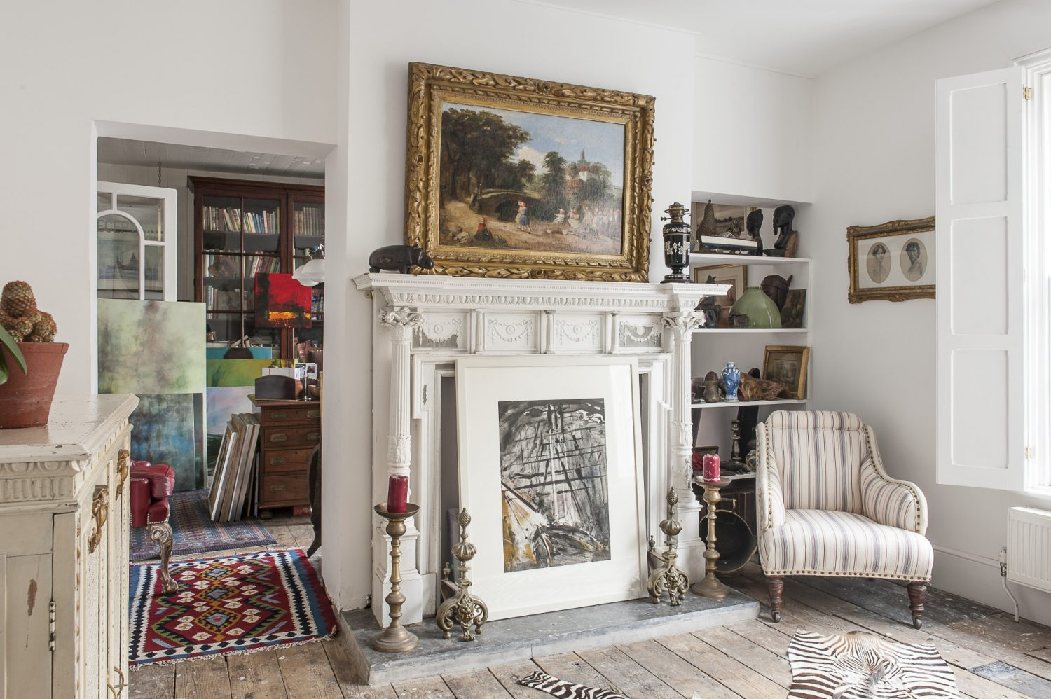 A matching pair of Adam fireplaces have been installed, one painted dark grey, the other white