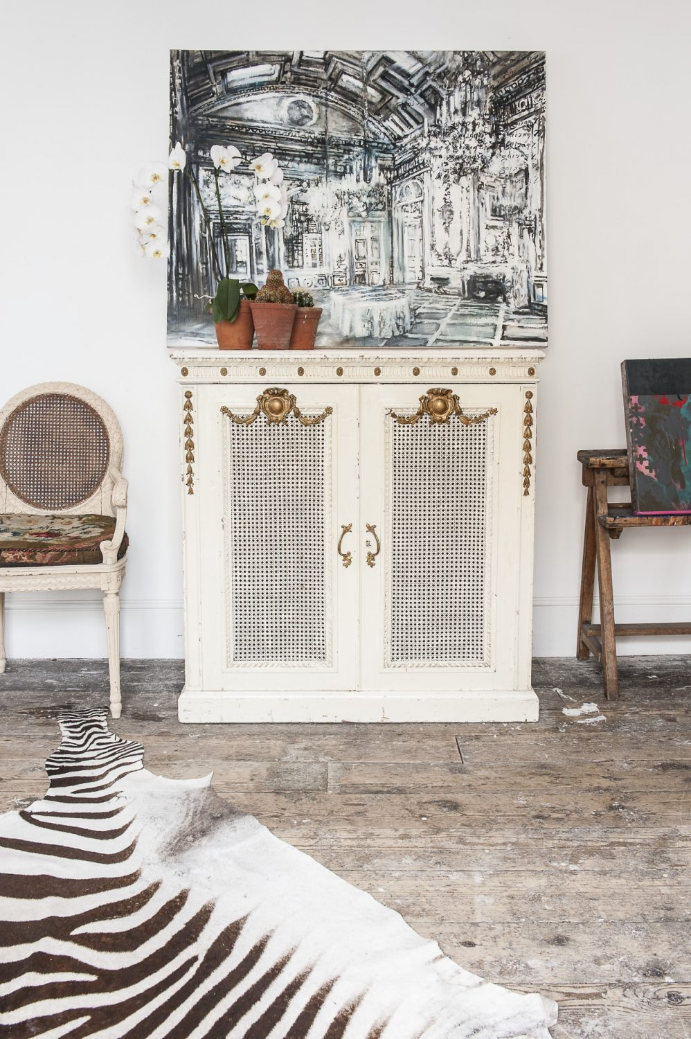 The intricate wrought-iron bed, gilded furniture, chandelier and zebra rug juxtaposed with the stripped floorboards and crisp white walls, work together to create a sense of faded luxury