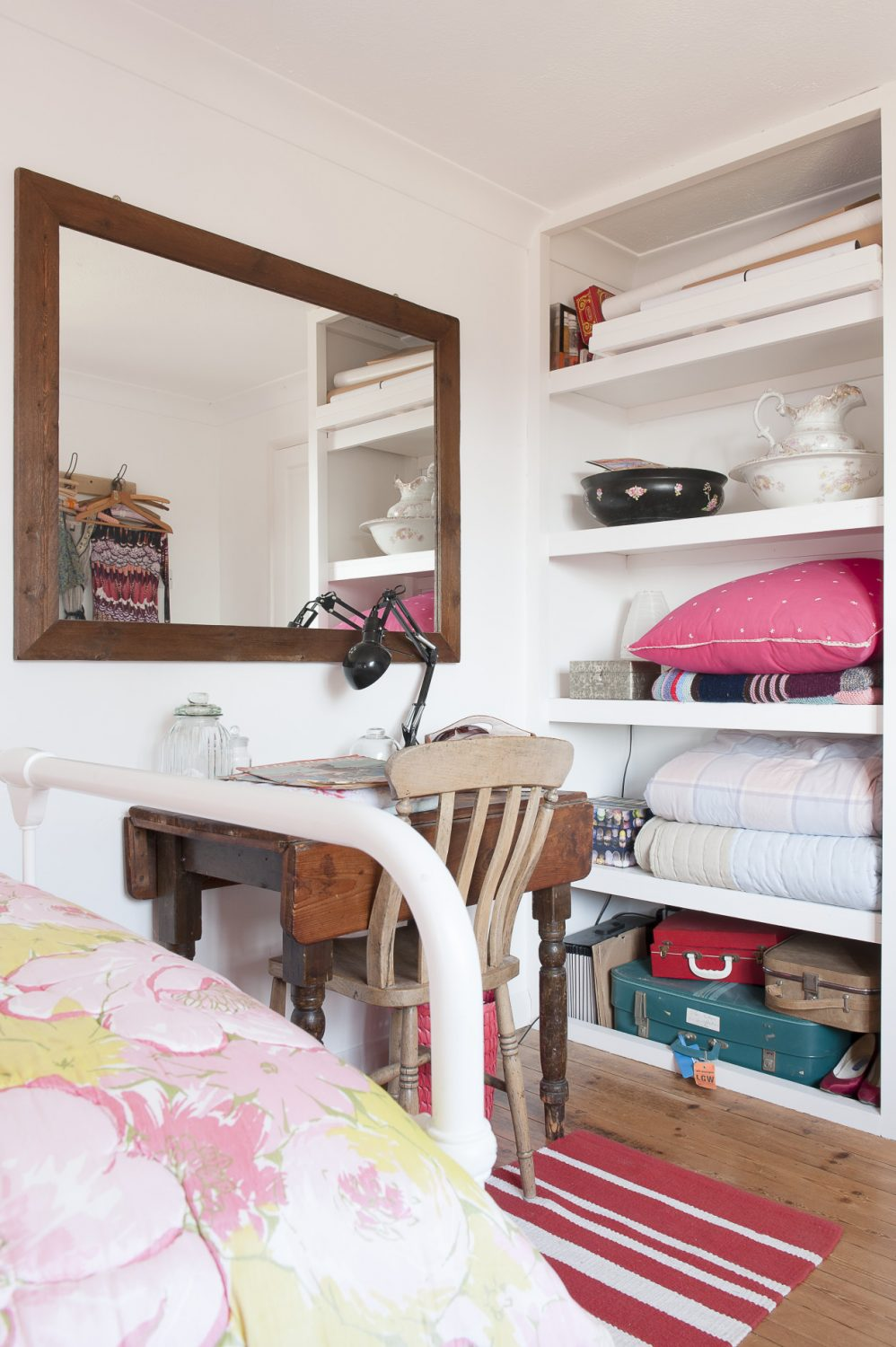 The bed in Liz's daughter's room is dressed with pretty pink flowered linen from Fenwick and a lovely quilt which was Liz's grandmother's. Piled by the bed are some more wonderful old suitcases – yet more useful storage