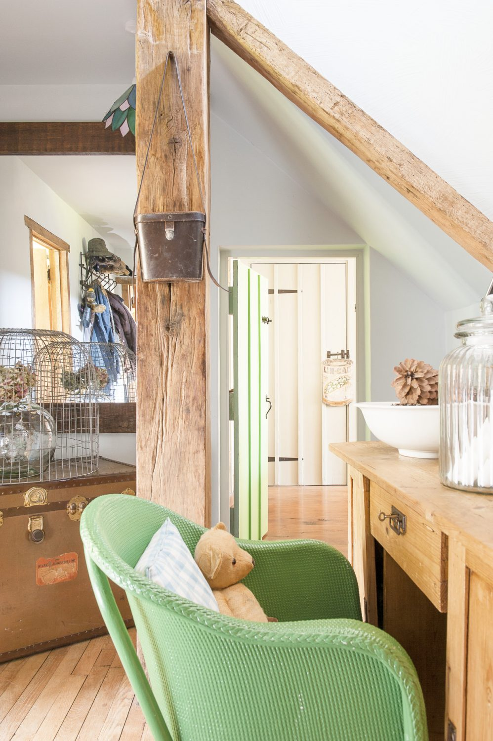 A tiny door in the dining room opens into the hallway. An unusually small pale green Lloyd Loom chair stands at the foot of the stairs in front of an antique pine desk. To the left stands an old travelling trunk topped by a wire garden basket upside down over a vase