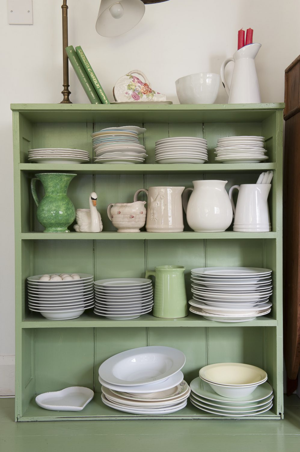 Stacks of pristine plates and fresh eggs from Liz's chickens are easily accessible from this painted green shelving unit
