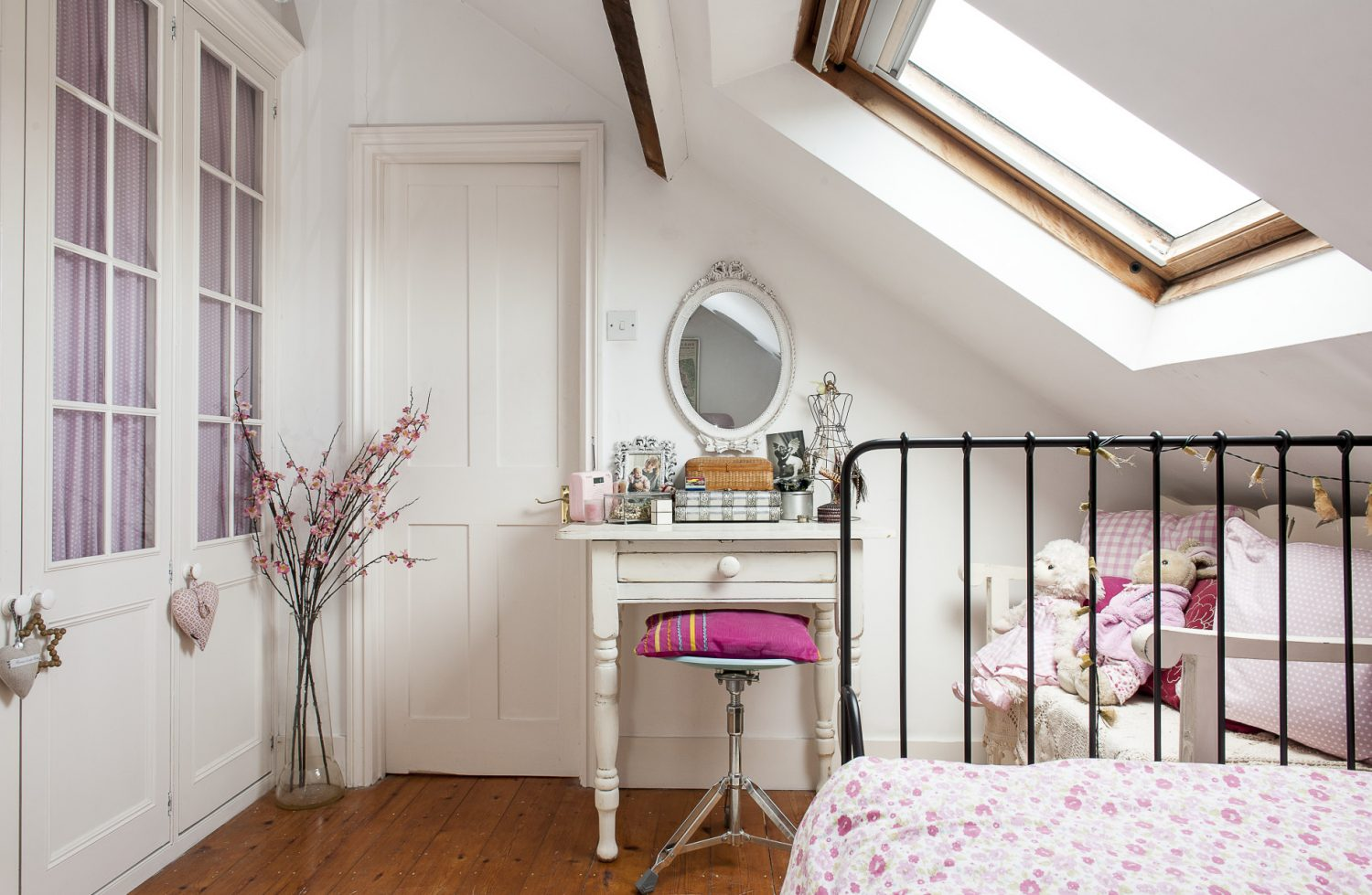 Right up in the eaves of the house, daughter Hannah's room is decorated in delicate pink and white with a wrought-iron Ikea day bed dressed with a pink floral cover. The elegant white dressing table, originally stripped pine, was given to Diana by her mother
