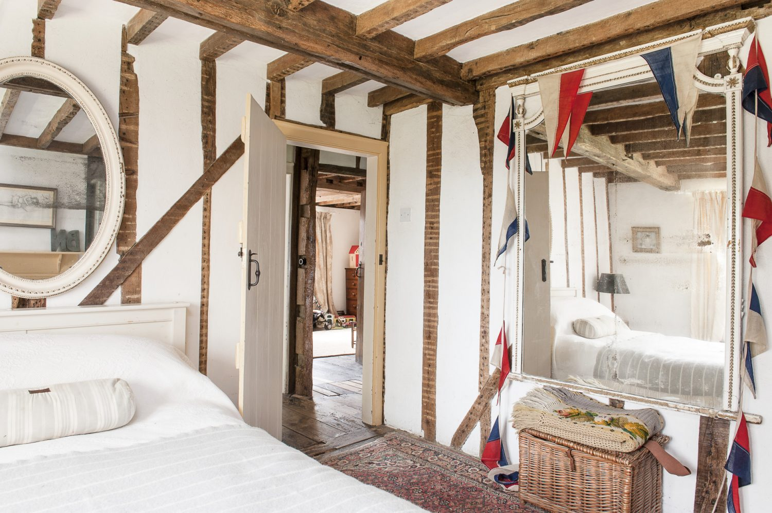 Nick and Bella's bedroom is the one room in the house that is virtually unchanged from the day they walked in. An ancient Gustavian mirror bought in Liverpool is hung with old bunting from Foxhole Antiques