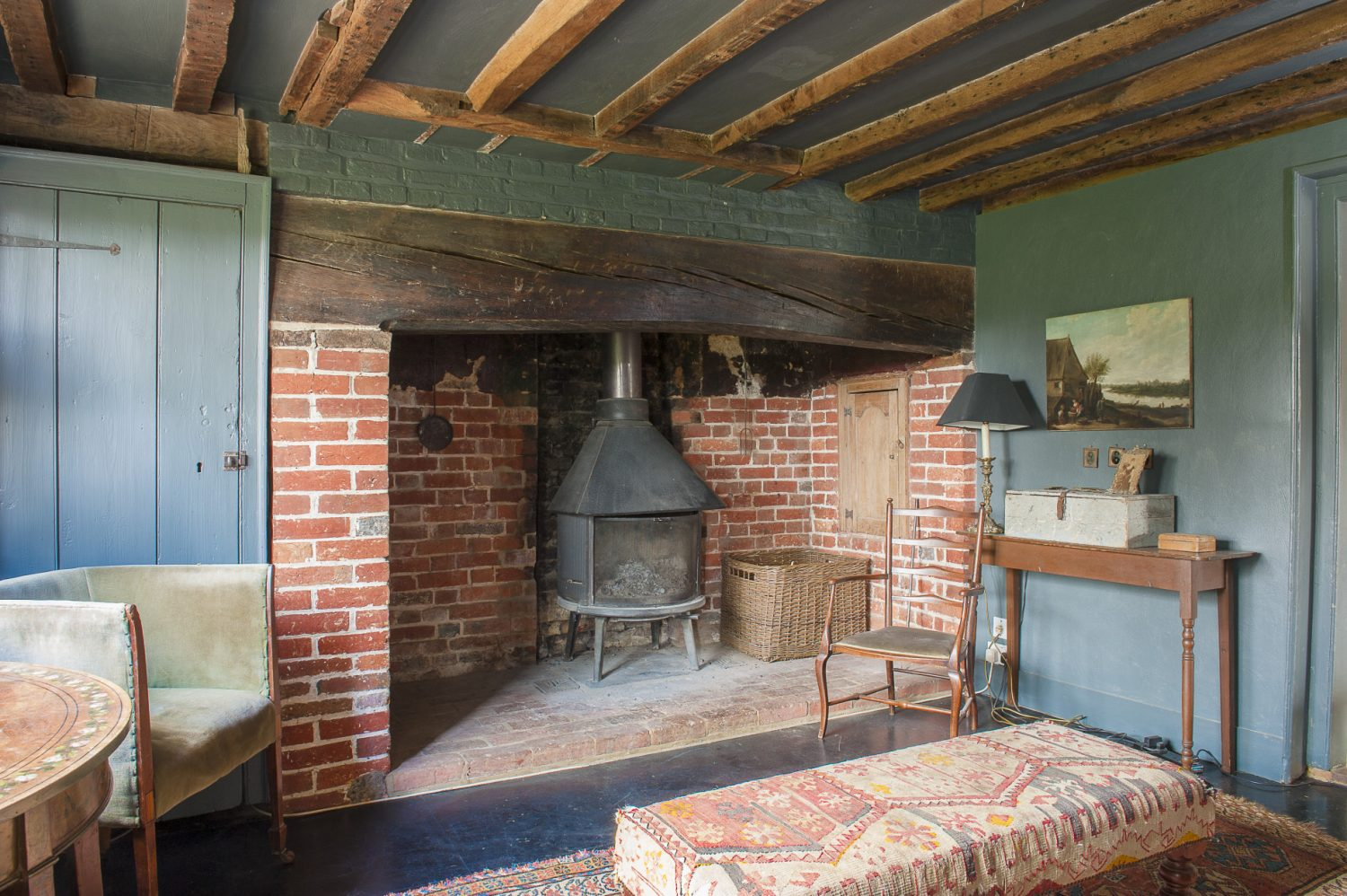 The second sitting room features painted hardwood floors and the walls and woodwork are painted a deep Farrow & Ball Down Pipe grey