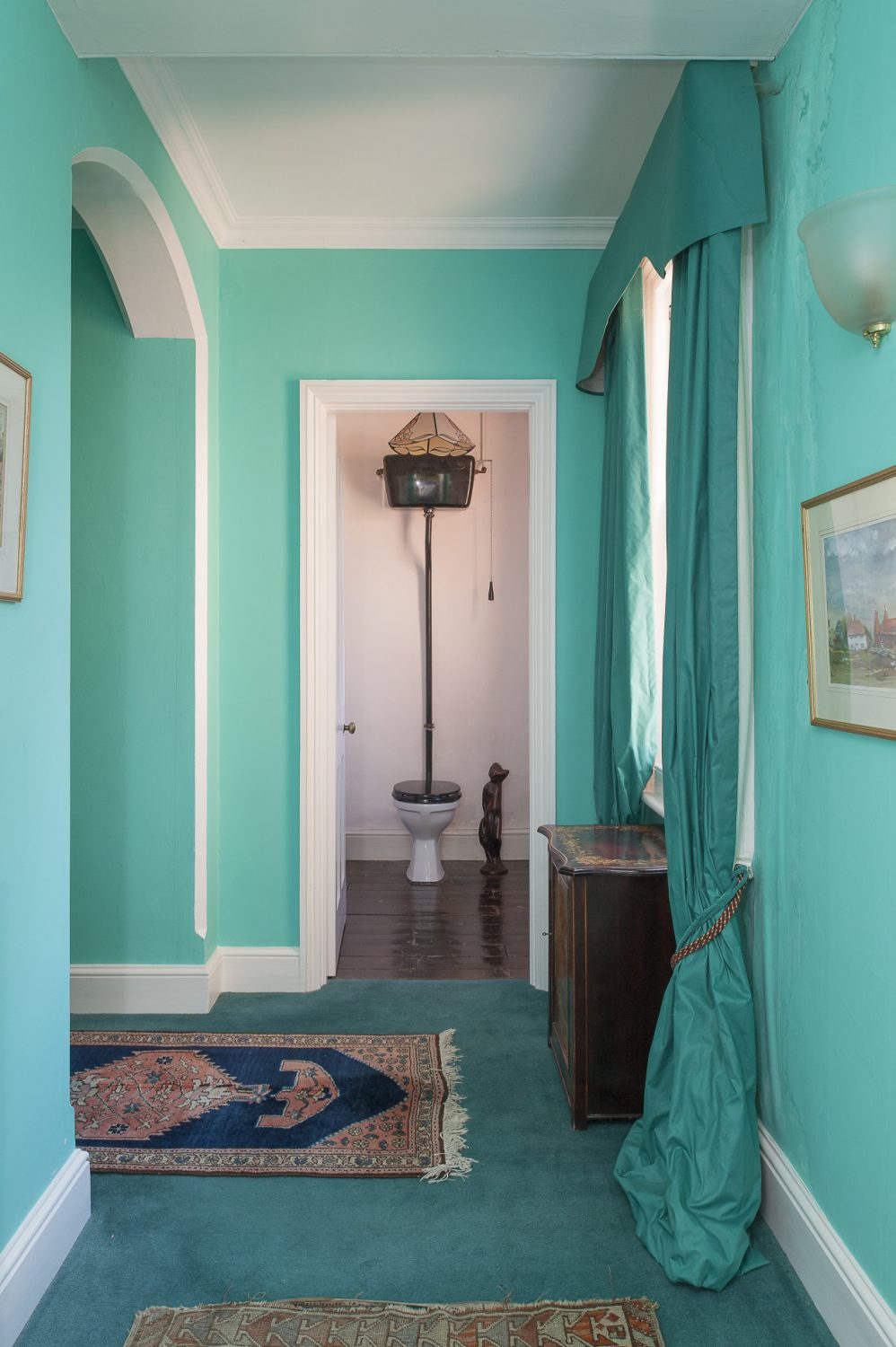The rich turquoise that Louise has chosen to paint the upstairs corridors sets off the dark inlaid wood furniture