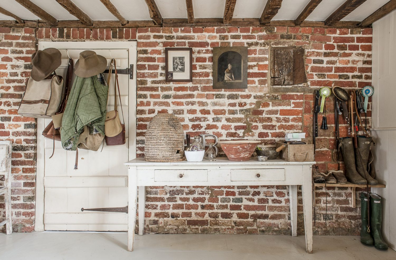 On the exposed brick wall opposite the Rayburn, interesting finds are grouped together on a table by the front door, including an old wicker beehive