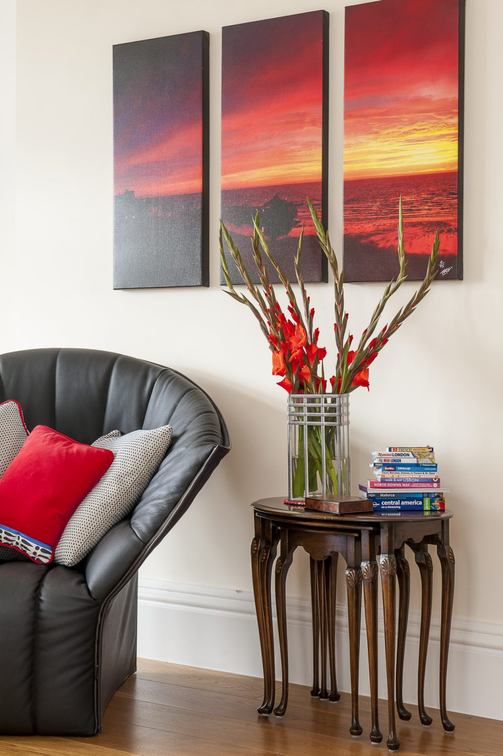 Accents of strong colour work well in the large, light filled rooms. Here, the vibrant red of a photographic triptych of a coastal sunset at Folkestone is echoed in the soft furnishings and crimson gladioli