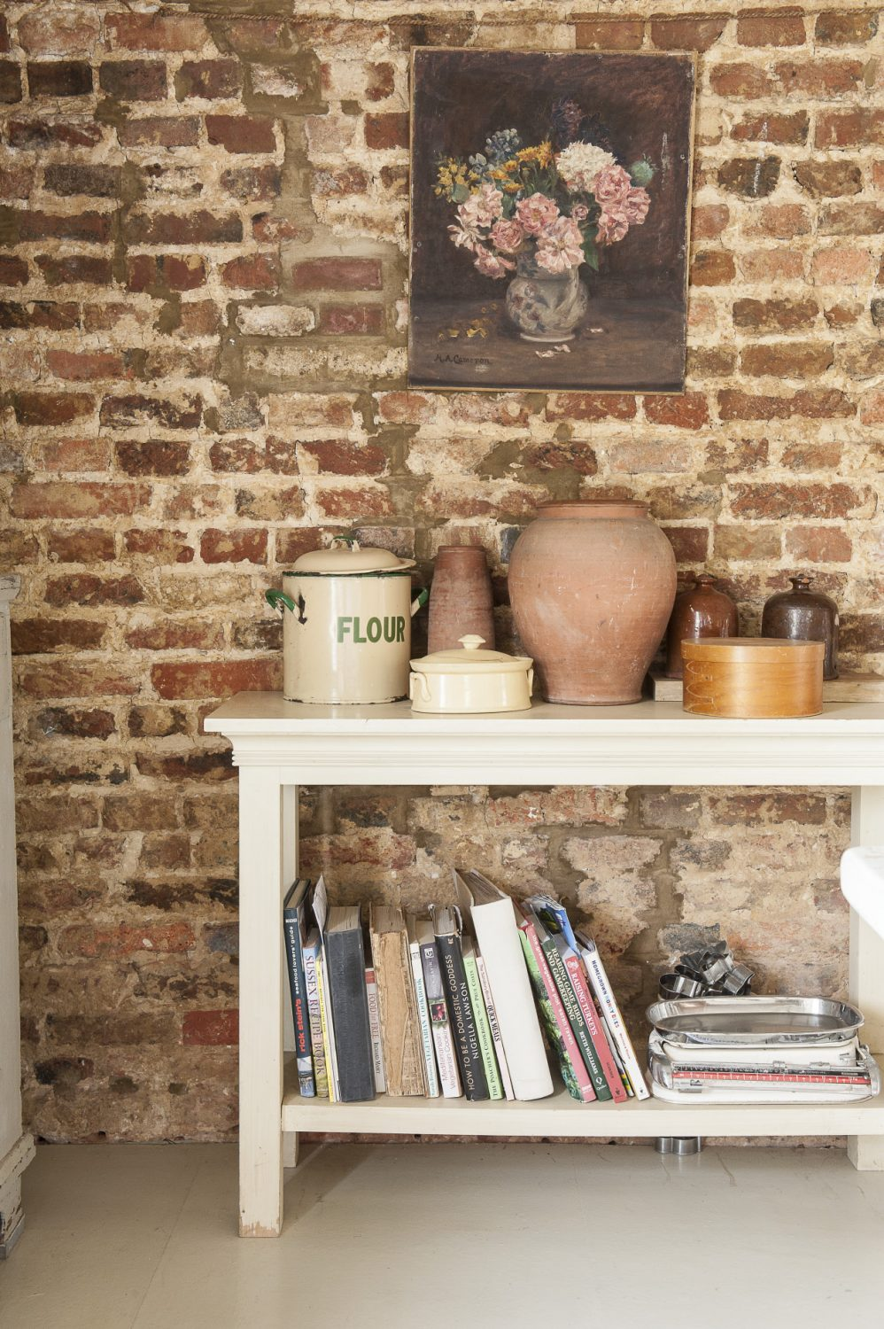 Recipe books and earthenware containers line a unit in the kitchen