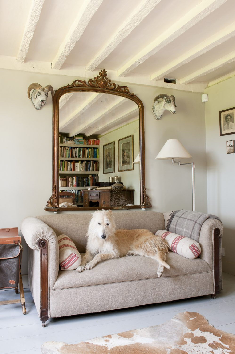 Books climb either side of the fireplace while across the room, above the sofa, is a huge gilded French overmantle mirror flanked by two strangely comical painted goat skulls from Foxhole Antiques in Hurst Green