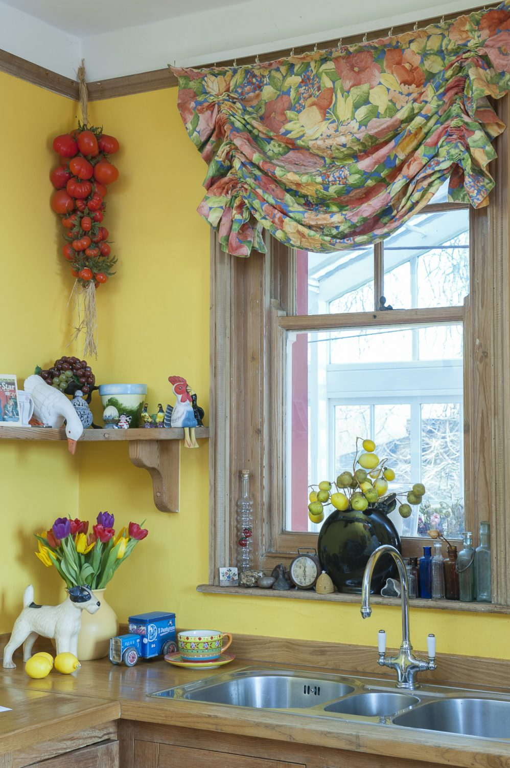 A kitchen window looks out into the bright conservatory