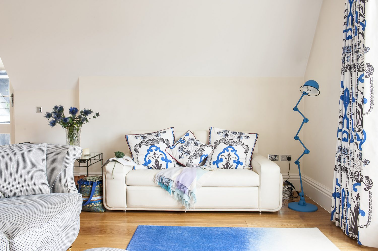 The bright white walls of the living room are highlighted with touches of blue