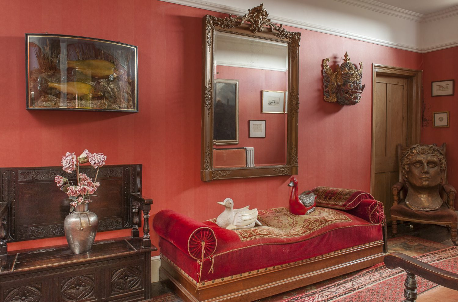 Mounted on the wall of the deep red hallway is a fierce Thai mask, two fat fish in a case and a French mirror the couple brought back from France. In one corner a chair is occupied by a giant Roman head from a film set