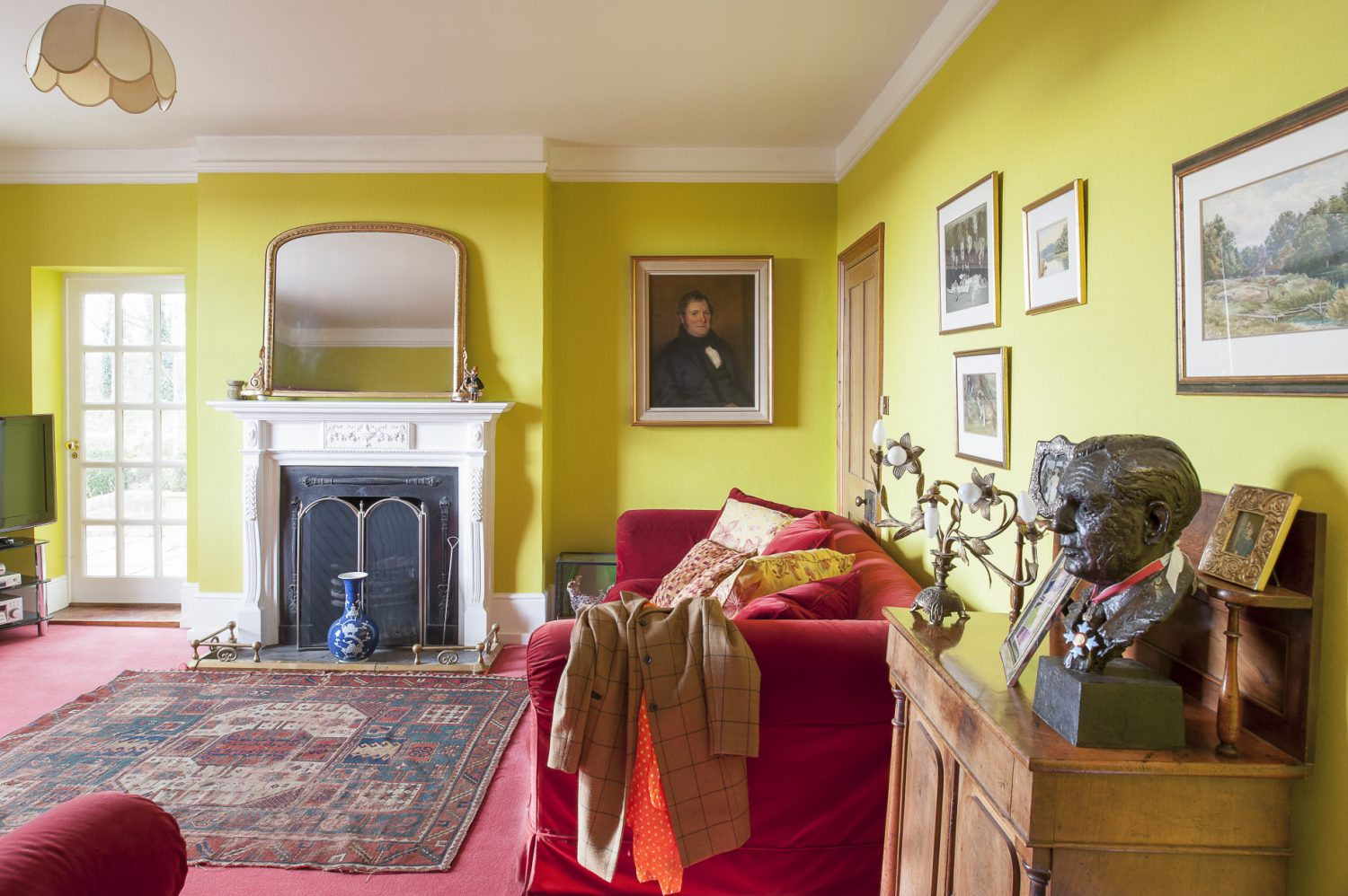 Over the drawing room fireplace is a Louis Philippe mirror and, flanking it, a portrait of Alex's great-grandfather nicely complemented by a bronze bust of his father on a cabinet by the door