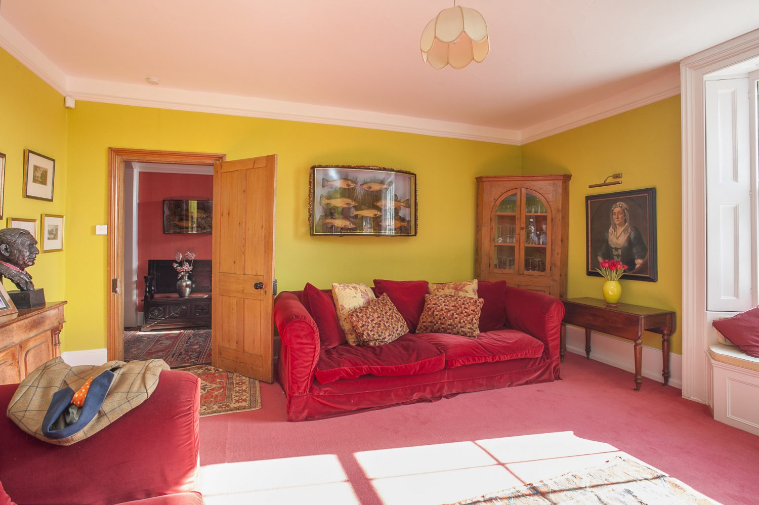The drawing room features two deep red velvet sofas that Louise found on eBay for £200