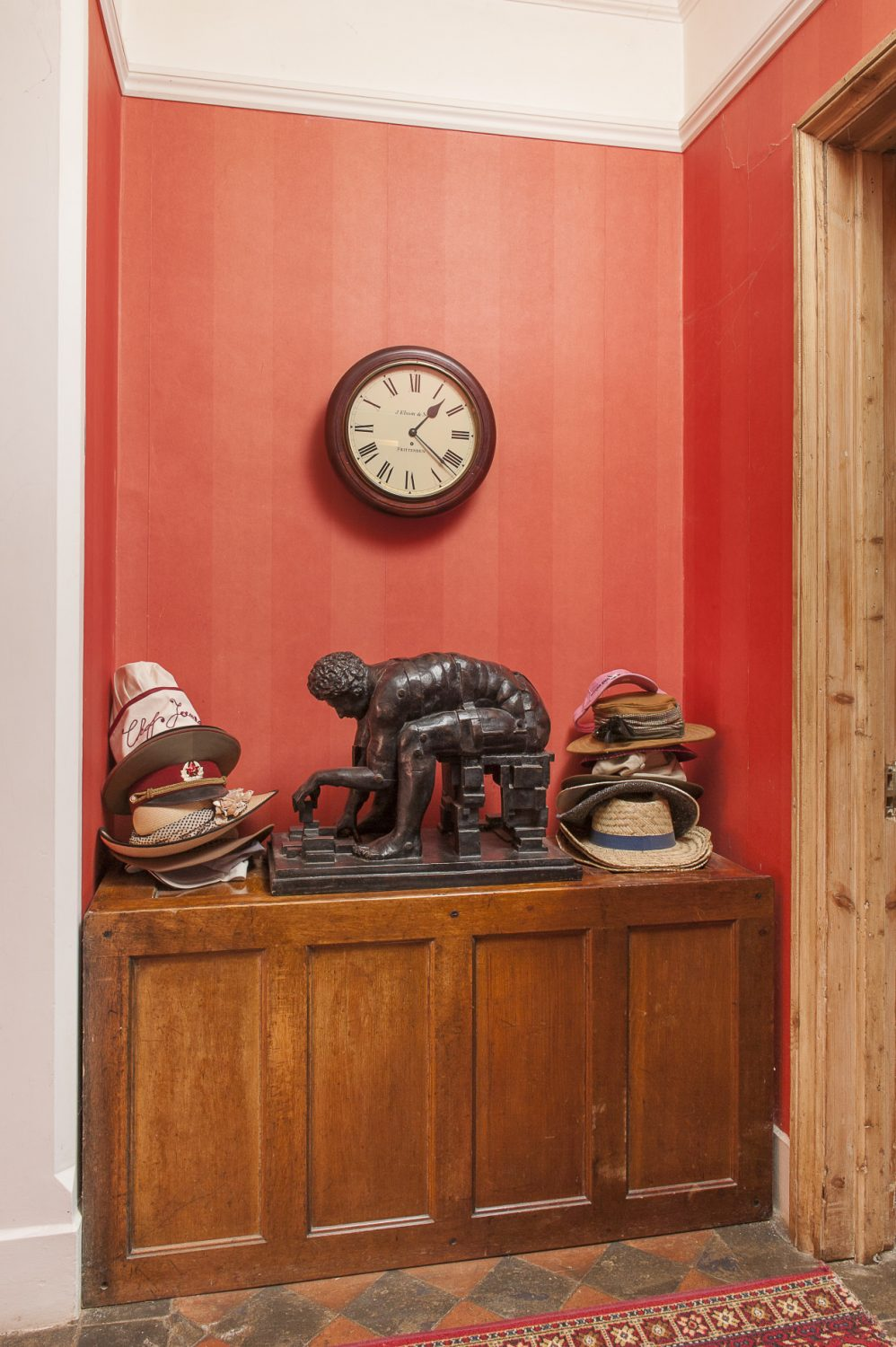 A bronze sculpture sits in between a collection of hats by the kitchen