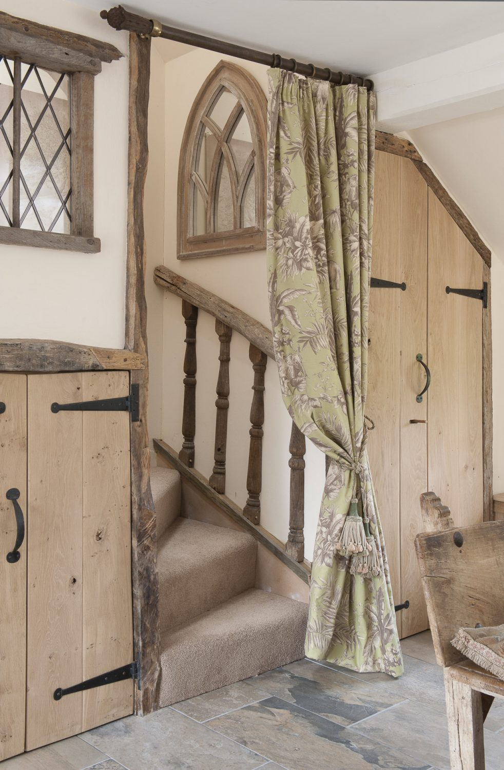 The stairway is also framed in ancient oak and climbing up the first few steps are oak spindles left over from the grand reclaimed staircase that now graces her own barn home. Above the spindles is a gothic window mirror