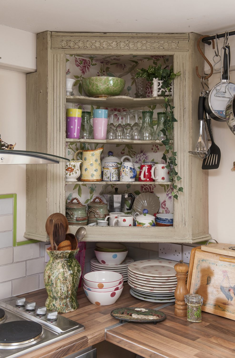 Over the kitchen surface is a corner cupboard which Caroline distressed herself in a pale green. She removed the doors to show the serpentine shelves and papered the interior