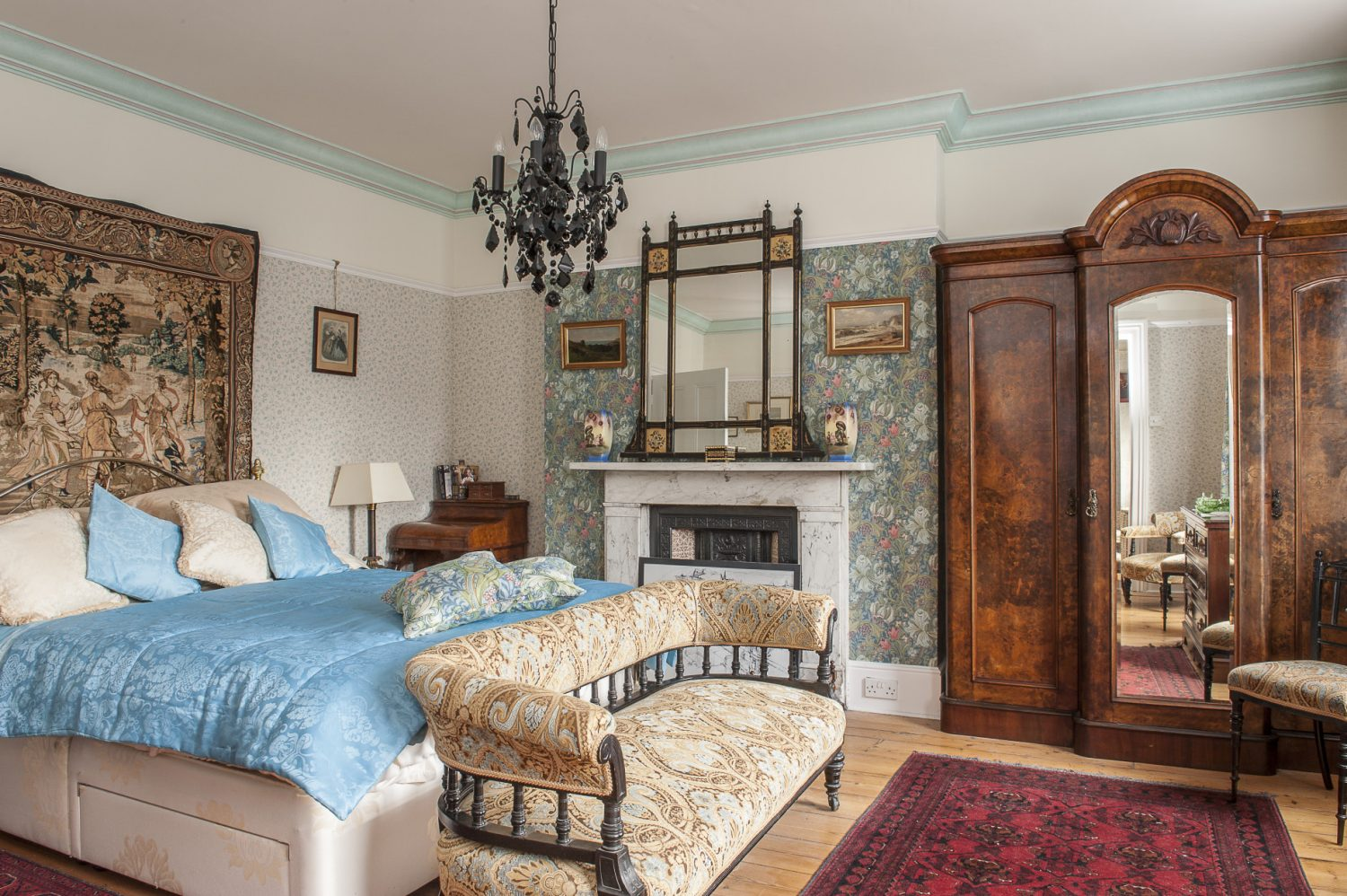 Ken and Irene's own bedroom has been modernised with a black glass chandelier which ties together the dark woods of the furniture with the contrasting pale florals of the soft furnishings and wallpaper