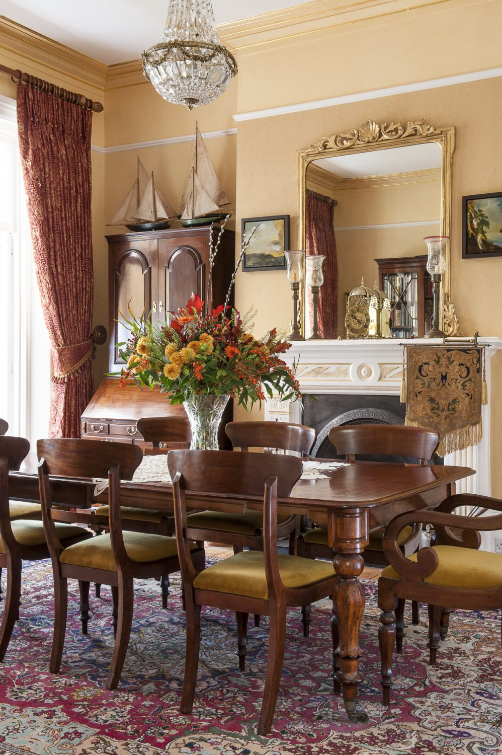 In the formal dining room, above the fireplace, is an elegant 19th century double action brass timepiece. Behind the clock is a Victorian gilt mirror, the twin of which tops a fireplace in Osborne House
