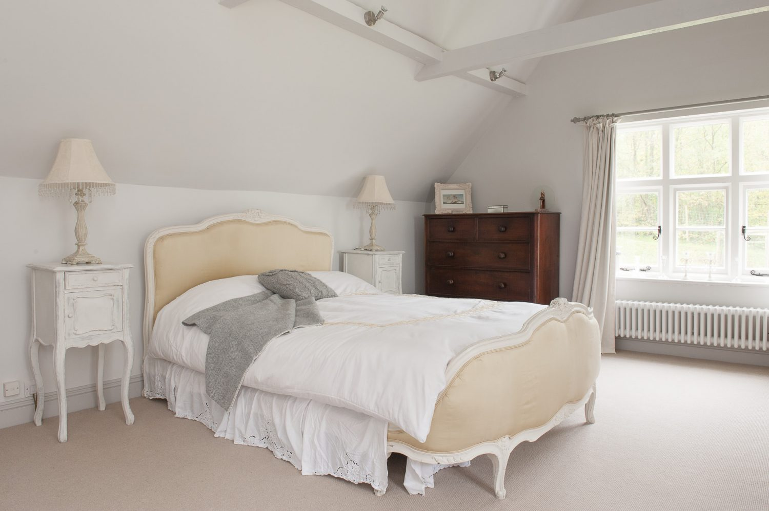 The couple have removed the ceiling in the bedroom and created a new and dramatic vaulted space, the perfect setting for the grand French bed from 'Tasha Interiors
