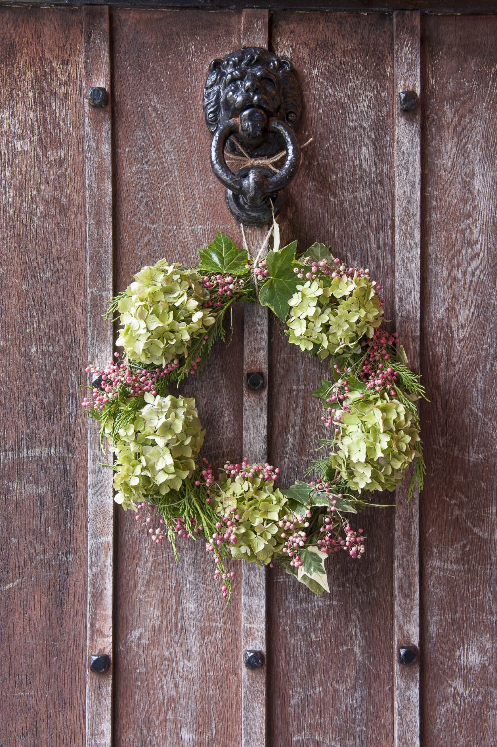 The pink peppercorn and hydrangea wreath greeting visitors to Alli's home was created by Sophie Hill from Flowers at the Stables