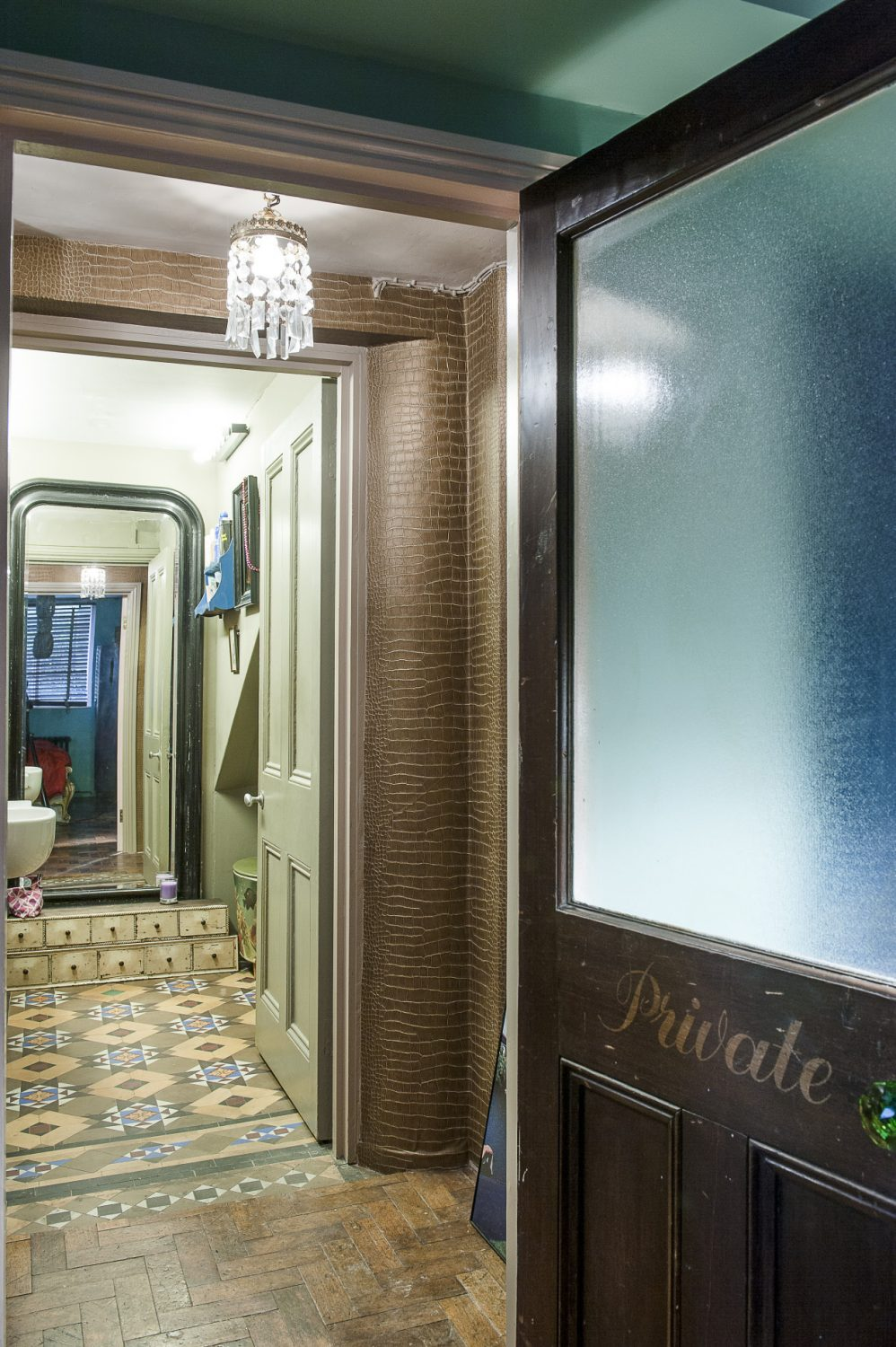 An old glass pub door with 'Private' etched on it, found on eBay, leads into the bedroom