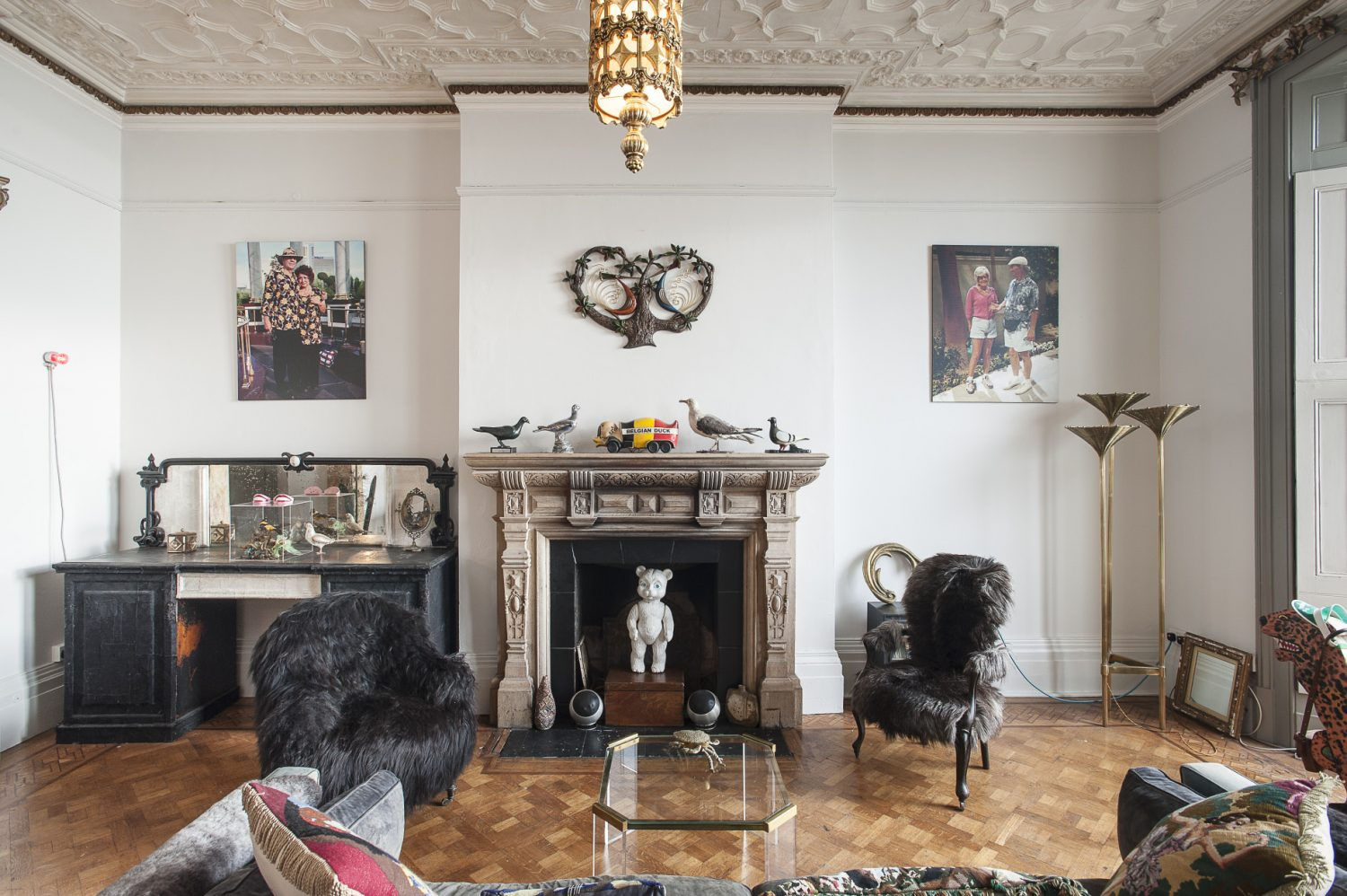 In front of the fireplace stands an ethereal 1970s Lucite coffee table, on which crouches a brass crab ashtray. A French cabriole armchair has been reupholstered in silky black goatskin